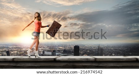 Young pretty woman walking with suitcase in hand