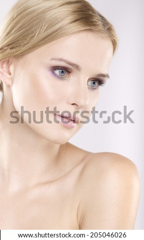 Young pretty woman with beautiful blond hairs and multicolor makeup isolated on white background - stock photo
