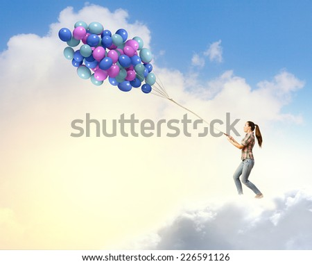 Young pretty woman with big bunch of colorful balloons - stock photo