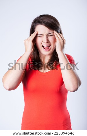 Young pretty woman with headache screaming in pain - stock photo
