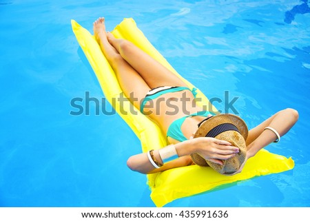 Young pretty woman with perfect tanned body lying on yellow air mattress in the pool - stock photo