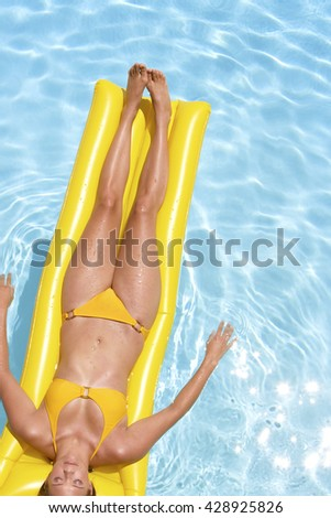 Young pretty woman with perfect tanned body lying on yellow air mattress in the pool in summer and having fun
