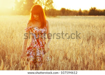 Young pretty woman with red hair at the field of wheat - stock photo