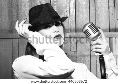 young pretty woman with sexy lips singing into silver studio microphone in retro hat and bow on shirt, closeup, black and white