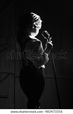 young pretty woman with sexy stylish cloth singing into silver studio microphone in retro hat braces and pants in darkness, black and white
