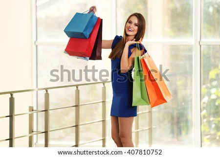 Young pretty woman with shopping packages  in the shop - stock photo
