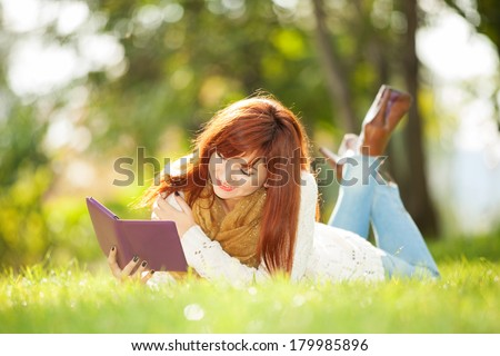 Young pretty woman with tablet in the park - stock photo
