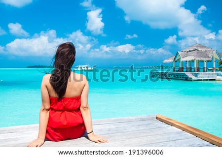 Young pretty women in red dress enjoying the tranquil sea view - stock photo