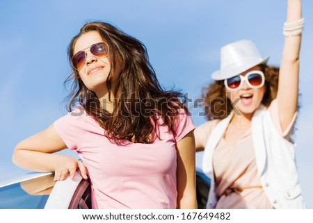 Young pretty women leaning out of car window