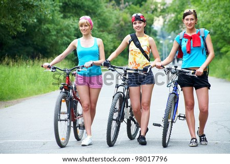 Young pretty women  walk  with  bicycle  along road in green park - stock photo