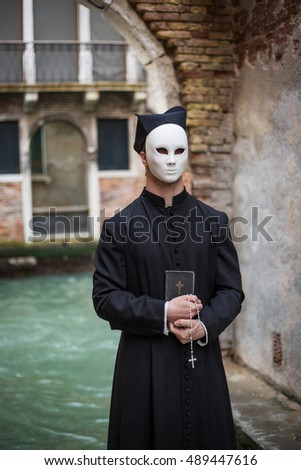 young priest in venice wearing mask  in front of canal