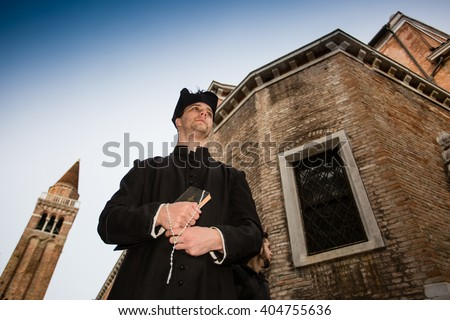 young priest in venice with church - stock photo