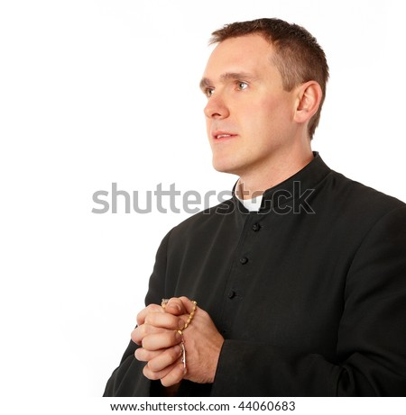 Young priest with rosary in his hands - stock photo