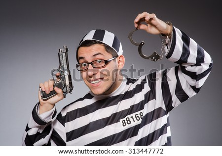 Young prisoner with cuffs and handgun against gray - stock photo