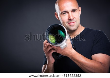 Young, pro male photographer in his studio during a photo shoot (color toned image; shallow DOF) - stock photo