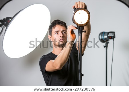Young, pro photographer setting lights in his well equipped studio before a photo shoot (color toned image; shallow DOF) - stock photo
