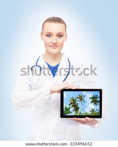 Young, professional and cheerful female doctor on blue background showing resorts on tablet. - stock photo