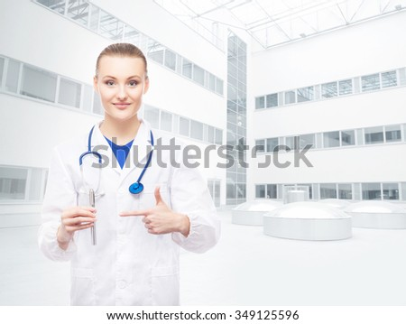 Young, professional and cheerful female doctor suggests using electronic cigarettes over hospital background. - stock photo