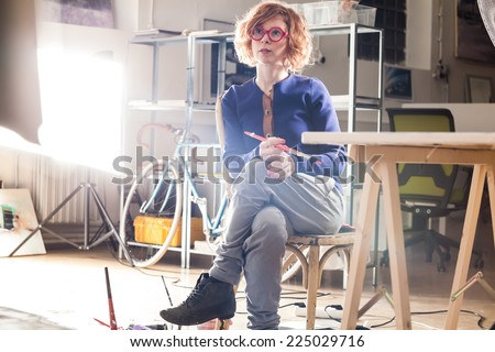 Young professional artist smiling and holding brush in her industrial studio. Color toned image. Soft light. - stock photo