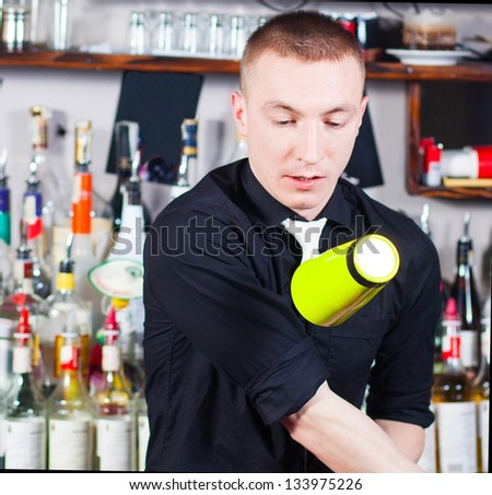 Young professional barman in action with shaker - stock photo