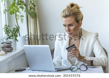 Young professional business woman sitting at table using a laptop computer and a credit card to make a payment on the Internet. - stock photo