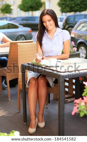 Young professional businesswoman sitting at table at cafe - stock photo