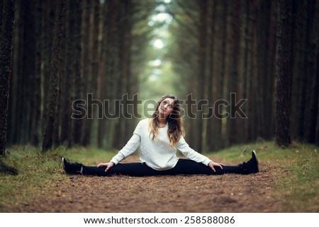 Young professional gymnast makes splits in the forest