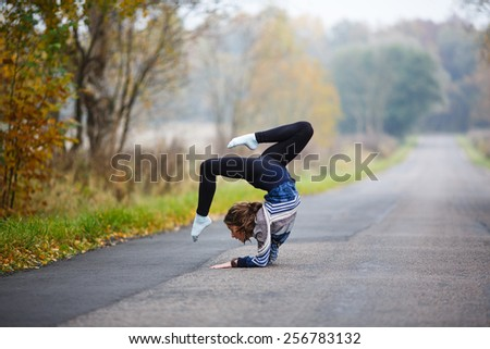 Young professional gymnast makes splits on the road at autumn time