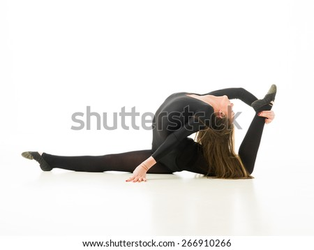young professional gymnast posing in split and stretching, on white background