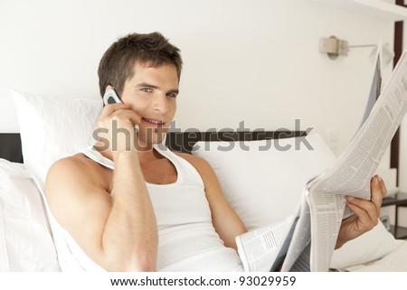 Young professional in bedroom, using a cellular phone and reading the paper. - stock photo