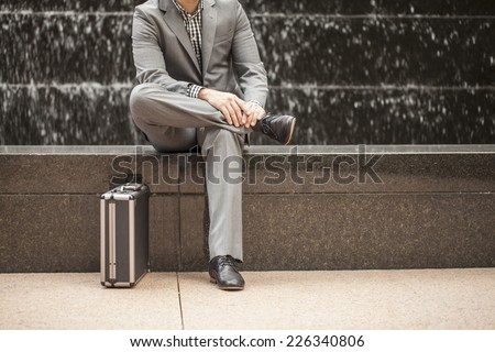 Young professional in business attire sitting down with water fall behind - stock photo