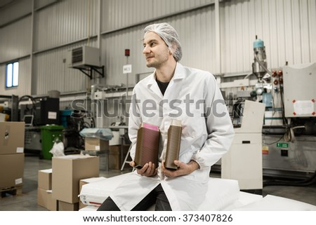 Young professional in warehouse for food packaging. Manager is sitting a holding the plastic boxes for paste in automated production line for food packaging in modern factory.  Color toned image.