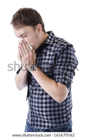 Young professional male standing blowing his nose into a tissue. Isolated image on white background. - stock photo