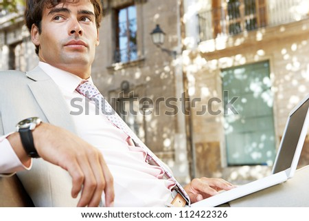 Young professional man using a laptop pc while sitting on a wooden bench in a classic city square.