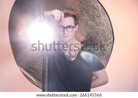 Young professional photographer working in the studio. Light. Studio portrait - stock photo