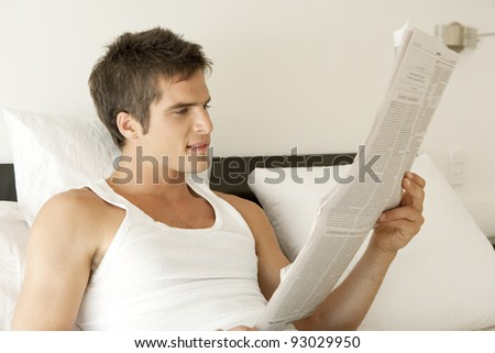 Young professional reading the newspaper in bed. - stock photo
