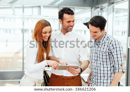 Young professionals standing and looking at a digital tablet - stock photo