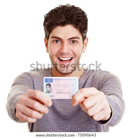 Young proud man with his European driving license - stock photo
