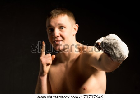Young pugilist throwing a punch during a boxing fight with his bandaged fist as he makes a gesture with his finger, dark dramatic image in the shadows - stock photo
