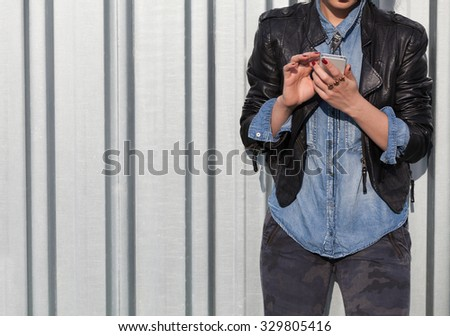 young punk style blond lady leaning on wall and using her mobile phone - stock photo