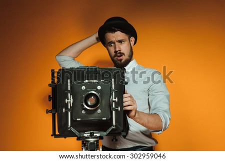 Young puzzled man in hat as photographer with retro camera on an orange background - stock photo