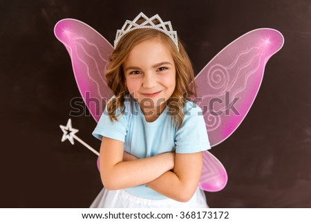 Young queen fairy with pink wings behind the back and a white crown on her head holding a cross hands on breast against dark background - stock photo