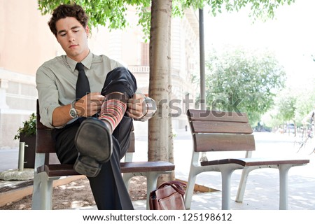Young quirky businessman pulling up his socks while sitting on a bench in the city, outdoors. - stock photo