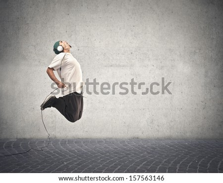 young rapper jumps and listens to music on gray background - stock photo