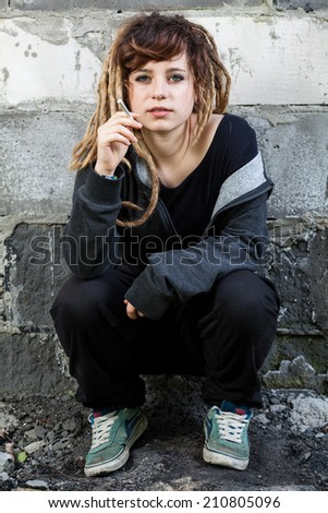 Young rastafarian girl in dreadlocks smoking weed - stock photo