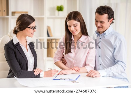 Young realtor explain lease agreement to young couple. - stock photo