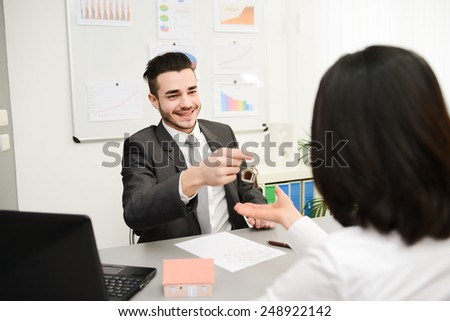 young realtor in transaction with buyer at office - stock photo