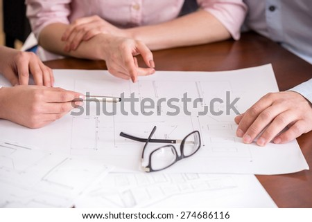 Young realtor showing contract with floor layout in an apartment to a young couple. - stock photo