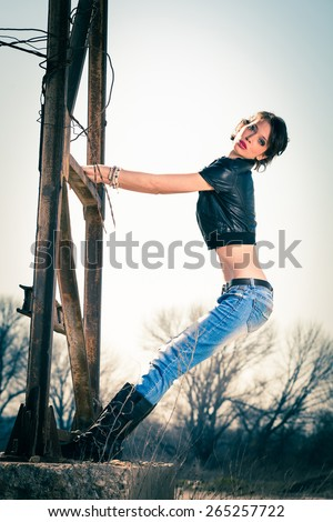 young rebel woman in blue jeans, leather boots and leather jacket outdoor shot on old metal construction, full body shot - stock photo