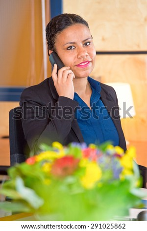 Young receptionist of a large cooperation taking calls on a phone - stock photo